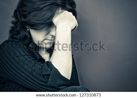 Blue toned portrait of a depressed woman - stock photo