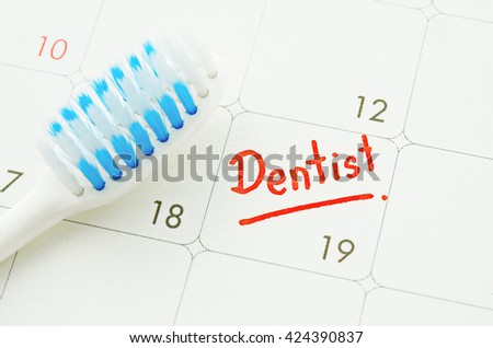 Blue toothbrush on dentist appointment reminder on a calendar page - stock photo