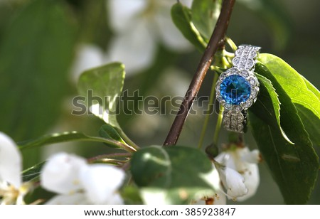 Blue topaz diamond engagement wedding ring nestled on a branch - stock photo