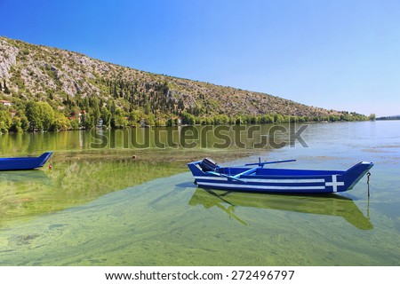 Blue traditional old wooden fishing boat with Greece flag in the lake Orestiada in Kastoria city of northern Greece - stock photo