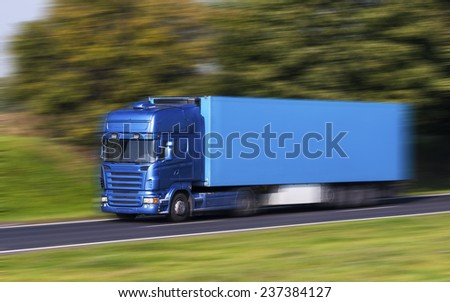 Blue Truck on a fast express road, motion blur - stock photo
