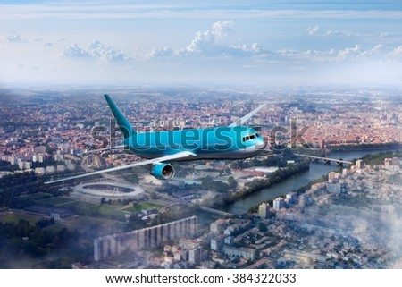 Blue - turquoise aircraft. Plane flying over residential areas of the city, the river and the stadium. - stock photo