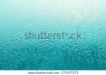 Blue Turquoise Filter Water Rain Drop on the Glass in Raining Season for Texture Background - stock photo