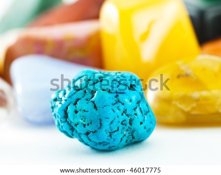 Blue turquoise gemstone in front of gemstone collection - stock photo