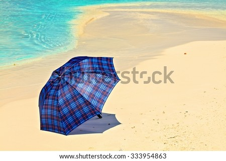 Blue umbrella is on a coral sandy beach, Maldives, The Indian Ocean - stock photo