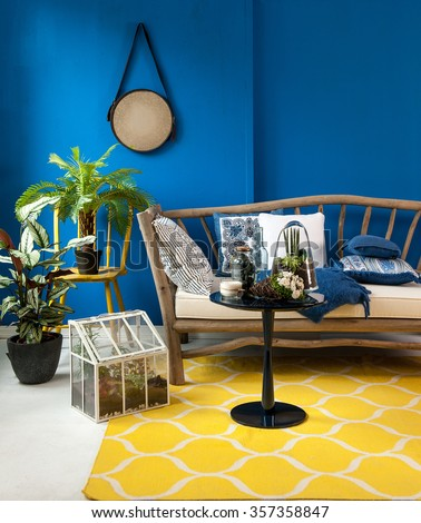 blue wall interior yellow rug and flower - stock photo