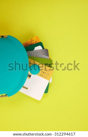 Blue wallet with pile of credit cards on green background - stock photo