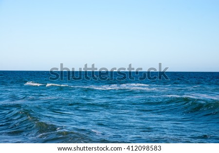 blue water of the ocean against the blue sky - stock photo