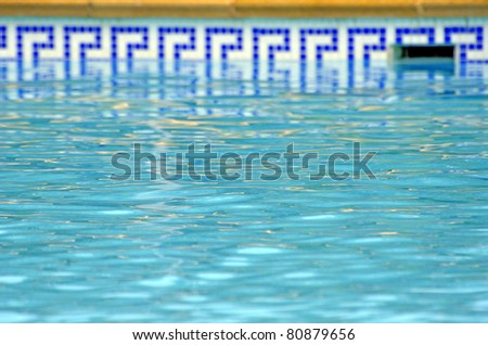 blue water of the pool and mosaic border - stock photo