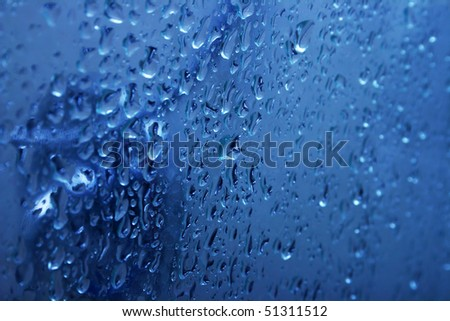 Blue water on glass door with bubbles as a background. - stock photo