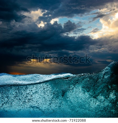 Blue water wave against dramatic storm clouds - stock photo