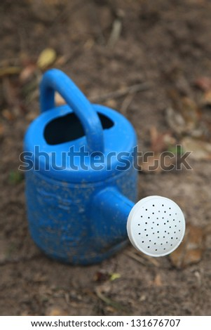 Blue watering pot in garden, closeup and shallow DOF. - stock photo