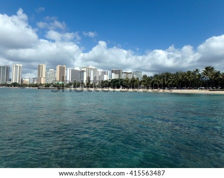 Blue Waters of Queens Beach and pier in Waikiki with Hotels in the distance.  Seen from water. - stock photo