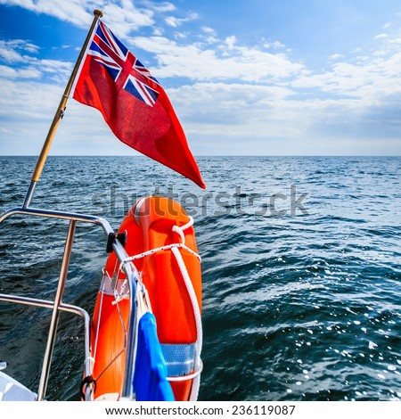 Blue wavy sea seascape. View from deck of yacht sailboat with british flag ensign and orange lifebuoy lifebelt. Safety travel. Yachting. - stock photo