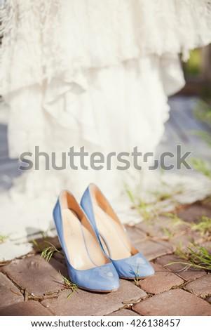 blue wedding shoes and wedding dress - stock photo