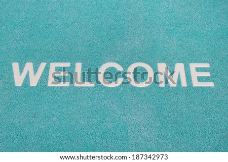 Blue welcome carpet, welcome doormat carpet - stock photo