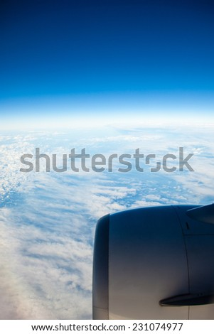 Blue white cloudy sky and engine. View from window of airplane flying in clouds. Skyscape cloudscape. Bird's eye. - stock photo