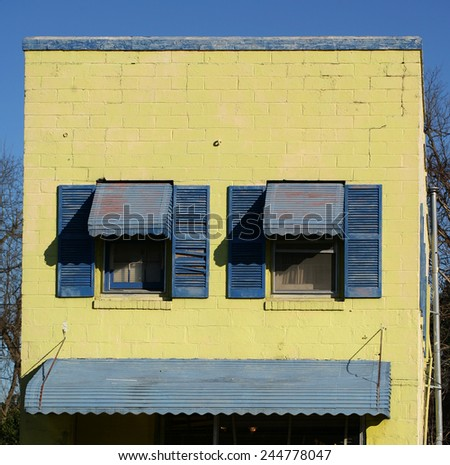 Blue window shutters on a weathered concrete yellow wall with awning - stock photo