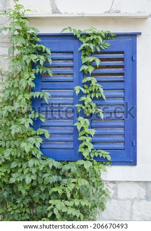 Blue window with shutters in old stone house, Croatia - stock photo