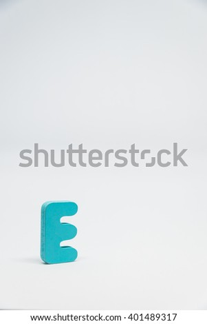 Blue Wooden alphabet E with white background in Vertical view - stock photo