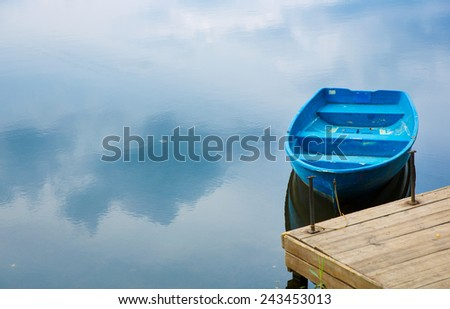Blue wooden boat near the pierce - stock photo