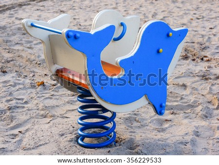 Blue wooden spring swing in dolphin shape - stock photo