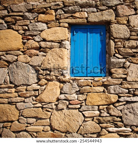 Blue wooden window and rock wall in Mykonos, Greece.  - stock photo