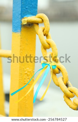 Blue-yellow bow on metal chain - colors of flag of Ukraine - stock photo