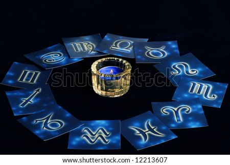 blue zodiacal cards in circle around a candle - stock photo