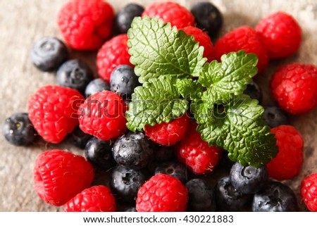 blueberries and raspberries on a stone background. Flat Lay. Top view. - stock photo