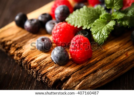 blueberries and raspberries on a wooden board background wood  - stock photo