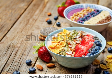 Blueberries and strawberries healthy smoothies breakfast bowls with nuts, seeds and fruits. toning. selective focus - stock photo