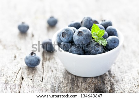blueberries in a bowl on wood - stock photo