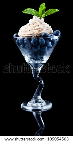 blueberries in a martini glass with fresh cream and green mint as a garnish isolated on a black background - stock photo