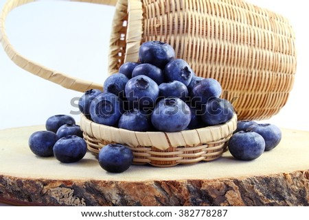 blueberries in bamboo basket on white background - stock photo
