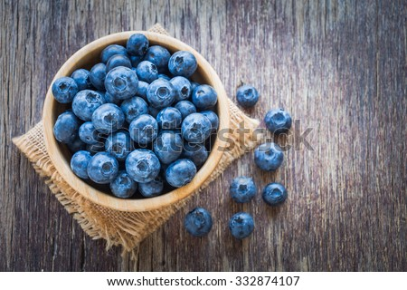 Blueberries in wooden bowl on wooden table background - stock photo