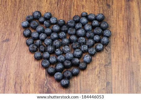 Blueberries on a wooden surface in a shape of a heart - stock photo