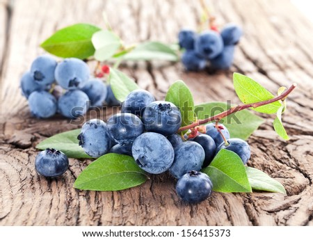 Blueberries with leaves on a wooden table. Studio isolated. - stock photo