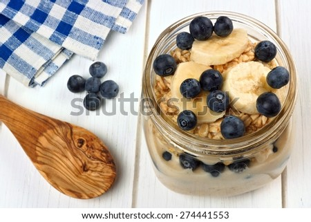 Blueberry and banana breakfast overnight oatmeal in a mason jar, with spoon on white wood - stock photo