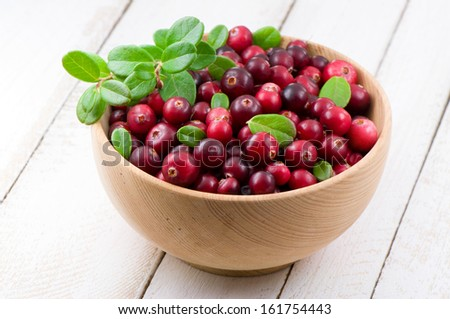 Blueberry and cowberry with green leaflets in wooden cup - stock photo