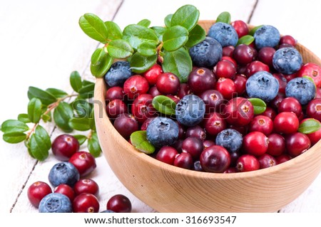 Blueberry and cowberry with green leaflets in wooden cup. - stock photo