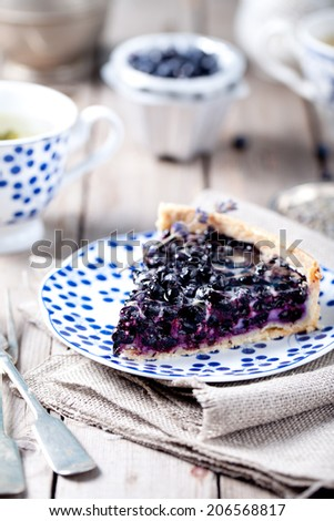 Blueberry, bilberry tart on a blue ceramic plate on a wooden background - stock photo