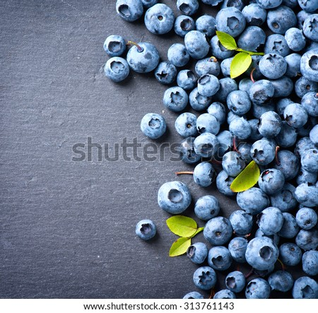Blueberry border design. Ripe and tasty blueberries with green leaves on dark background. Bilberries close-up. Copy space for your text. Healthy food concept - stock photo