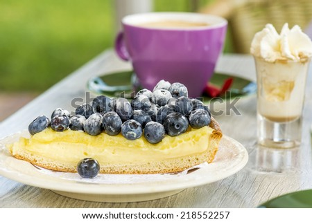 blueberry flan or pie, with coffee and whipcream. shallow depth of field - stock photo