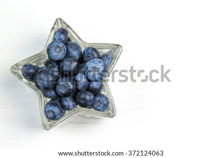 Blueberry in a star shaped bowl on white wooden background - stock photo