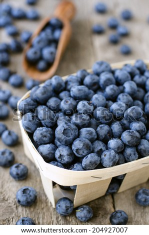 Blueberry in a wicker basket on the wooden table - stock photo