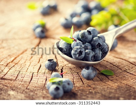 Blueberry in spoon on wooden table background. Ripe and juicy fresh picked bilberries closeup on Weathered Wood Boards for a Vintage Look. Blueberries close up.  - stock photo