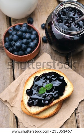 Blueberry jam on toast bread on wooden table - stock photo