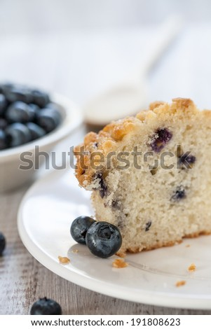 Blueberry muffin cut in half with bowl of blueberries and wooden spoon - stock photo