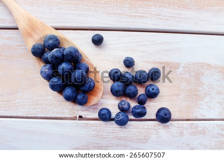 Blueberry on a Wooden Spoon on a Wooden Background, Close Up - stock photo